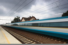 Fast train. Passing by (motion blur is used to convey movement; color toned image Royalty Free Stock Images