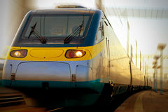 Fast train in motion. High speed train in motion crossing the railway station Royalty Free Stock Images
