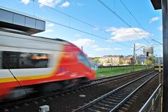 Fast train with motion blur. Train departing a  station and gathering speed Royalty Free Stock Photography