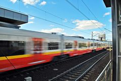 Fast train with motion blur. Train departing a  station and gathering speed Stock Image