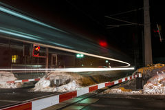 Fast train passing by railroad crossing Royalty Free Stock Image