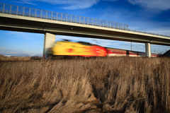Fast train passing under a bridge Royalty Free Stock Photos