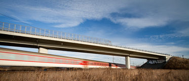 Fast train passing under a bridge on a lovely summer day Royalty Free Stock Photography