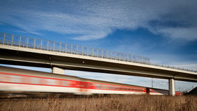Fast train passing under a bridge on a lovely summer day Stock Photography