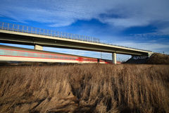 Fast train passing under a bridge on a lovely summer day Royalty Free Stock Images