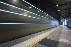 Fast train traveling through underground subway station. Passenger train speeding through an underground station of a urban city Stock Images