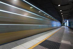 Fast train traveling through underground subway station. Passenger train speeding through an underground station of a urban city Stock Image