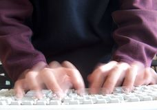 Fast typing. Person typing very fast on a keyboard - blurred royalty free stock photo