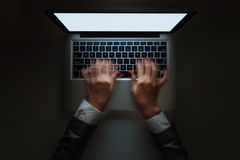 Fast typing. Blurred motion of hands typing on laptop late at night, view from above royalty free stock image