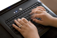 Fast Typist. Detail of a woman typing rapidly on a laptop keyboard Royalty Free Stock Images