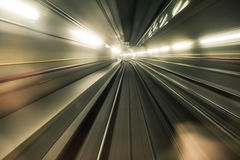 Fast underground train riding in a tunnel of the modern city Royalty Free Stock Images