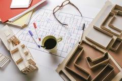 Fast utgift av byggnadsmodell- och skissninghjälpmedel på ett konstruktionsplan. Arkivfoton