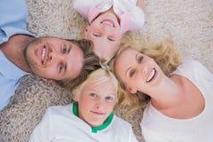 Fast utgift av familjen som ligger på mattan Fotografering för Bildbyråer