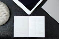 Fast utgift av kontorstabellen med anteckningsboken, minnestavlaPC:n, notepads kopierar arkivfoto