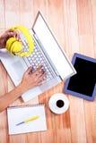 Fast utgift av kvinnliga händer som skriver på bärbar dator- och innehavhörlurar Arkivfoton