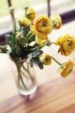 Fast utgift metad sikt av vasen av gula blommor arkivbild