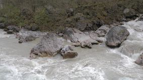 Fast water stream in mountain river with stones. Fresh cold water coming from the glacier. Nature landscape with trees. And river stock footage