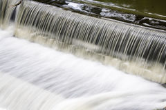 Fast weir. Fast water over a small weir Stock Image