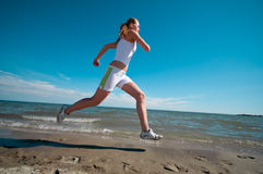 Fast woman running in sea coast Stock Photo