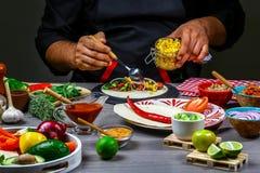 Fasta food kucharstwo Ręki przygotowywa tortilla opakunek z cięciami mięsa i warzywo sałatką, meksykański burito zdjęcia stock