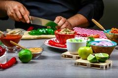 Fasta food kucharstwo Ręki przygotowywa tortilla opakunek z cięciami mięsa i warzywo sałatką, meksykański burito zdjęcie royalty free