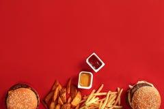 Fasta food naczynia odgórny widok Mięsny hamburger, frytki i bryłki na czerwonym tle, Takeaway skład Odgórny widok Zdjęcia Stock
