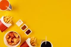 Fasta food naczynie na żółtym tle Fasta food francuza i pieczonego kurczaka ustaleni dłoniaki Bierze oddalonego fast food Fotografia Royalty Free