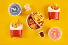Fasta food naczynie na żółtym tle Fasta food francuza i pieczonego kurczaka ustaleni dłoniaki Bierze oddalonego fast food Obraz Stock