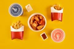 Fasta food naczynie na żółtym tle Fasta food francuza i pieczonego kurczaka ustaleni dłoniaki Bierze oddalonego fast food Zdjęcie Stock