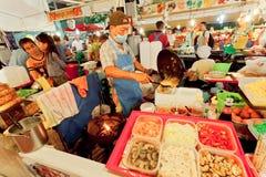 Fasta food sprzedawcy kucharstwo przy noc rynku różnymi posiłkami z owoce morza i świeżymi warzywami Obrazy Stock