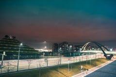 Fastar trafik i en väg och en bro i modern och futuristisk stad royaltyfria foton