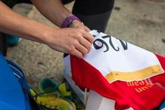Fasten Bib Number to T-Shirt before City Marathon Stock Image