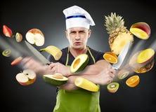 Fasten der Koch, der Gemüse im mitten in der Luft schneidet Stockbild