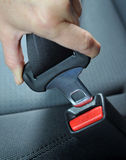 Fasten the seat belt. Closeup of a person snapping a seat belt in place stock photography