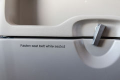 Fasten seat belt while seated sign on airplane Royalty Free Stock Photo