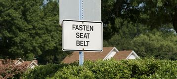 Fasten Seat Belt Sign. A sign instructs motorist to fasten their seat belts as prescribed by law Stock Photos