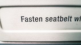 Fasten seat belts sign on tray table in flight royalty free stock photos