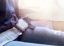 Fastened airplane seat belt and light coming from plane window. Stock Photo