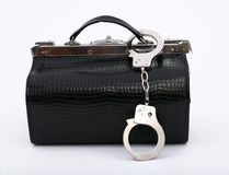 Fastened handcuffs pinned to black bag Royalty Free Stock Images