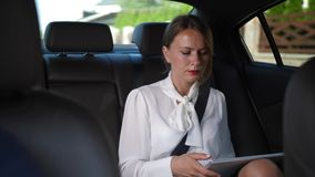 Serious woman using tablet going to work by taxi. Fastened with safety sear belt female in business clothes networking on tablet while riding in taxi to work stock video