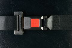 Fastened seat belt on black leather background, close-up. Safety. Concept Stock Photo