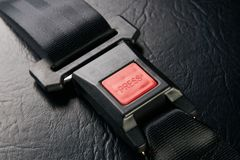 Fastened seat belt on black leather background, close-up. Safety. Concept Stock Photos