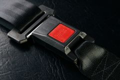 Fastened seat belt on black leather background, close-up. Safety. Concept Stock Images