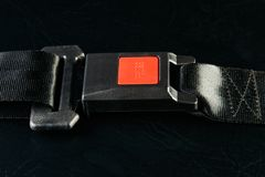 Fastened seat belt on black leather background, close-up. Safety. Concept Stock Image