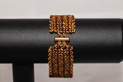 Fastener of a brown and gold hand stitched flat beaded bracelet. The fastener of a brown and gold hand stitched flat beaded bracelet royalty free stock photos