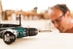 Fastener drive in focus and woodworker on background Royalty Free Stock Photo