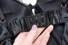 Fasteners black bodice in a female hand. Fashionable concept.  Stock Photo