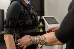 Fastening EMS suit. Male trainer fastening belt of EMS suit on woman stock image