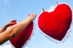 Fastening the heart-cushion with a clothes pegs stock photography