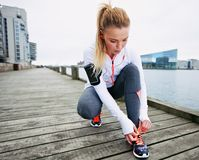 Fastening her shoelaces before the run. Fit and sporty young woman tying her laces before a run. Female runner tying her shoelaces while training outdoor royalty free stock images
